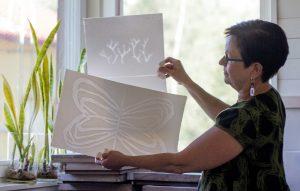 Sirpa kivilompolo valmistaa läpikuultavia kuvioita käsintehtyyn paperiin